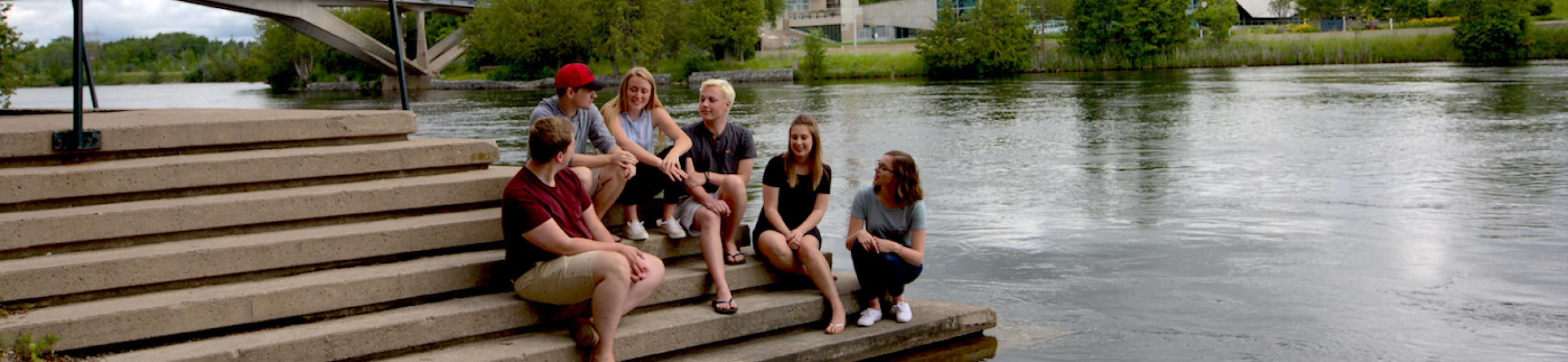 A group of students sitting on some concrete stairs by the river