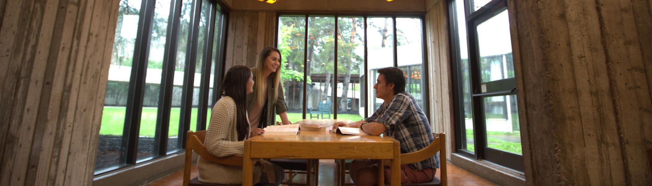 3 students sitting at a table surrounded by windows conversing with each other