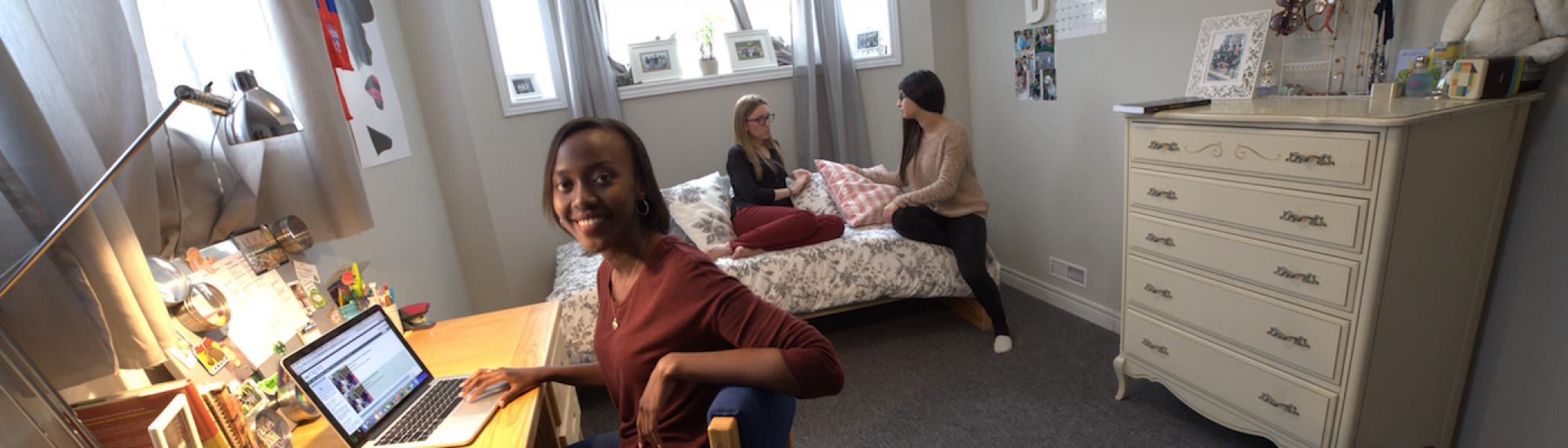 A girl sitting at her desk in her dorm room smiling with two girls sitting on her bed
