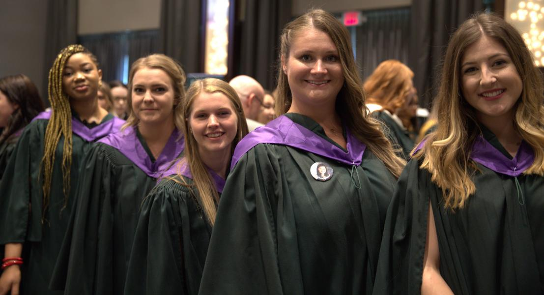 Group of students smile together in green graduation gowns