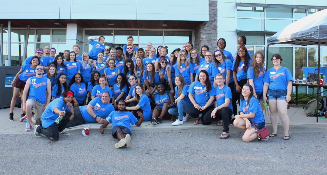 orientation leaders smile in front of campus in large group