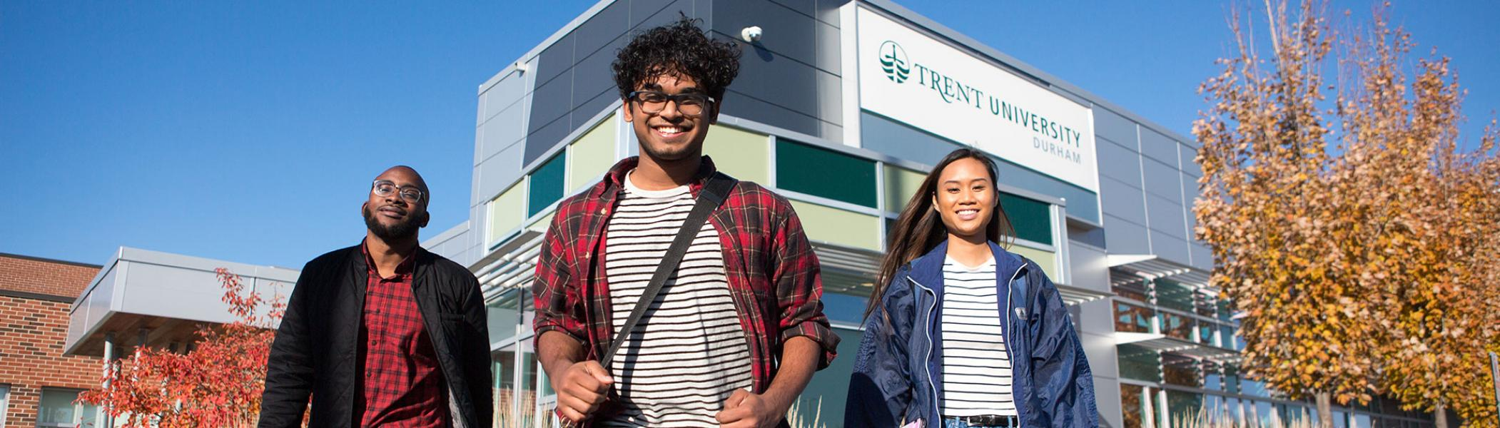 Trent University Durham students smiling to the camera in front of campus.
