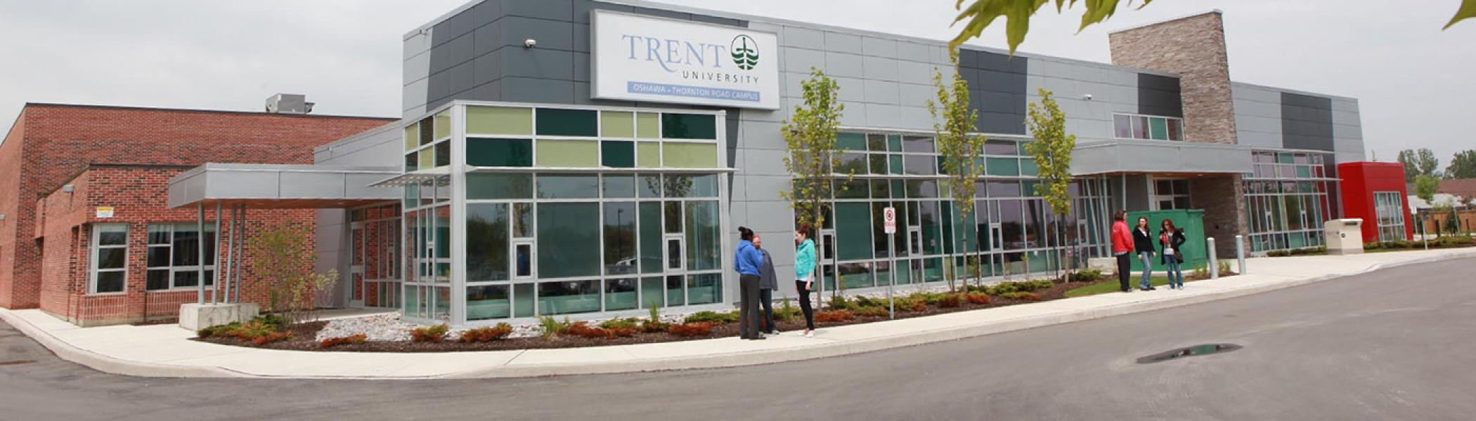 Two small groups of people are standing near the entrance of Trent University Durham Campus