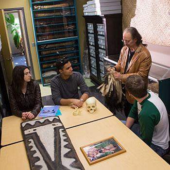 Professor showing students some artifacts in a classroom.