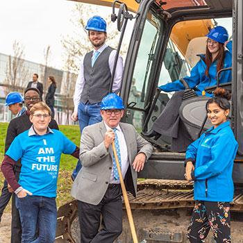 Students wearing hard hats standing in front of a tractor with President Joe Muldoon at the site of the Trent University Durham GTA expansion.