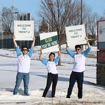 Trent University Durham students holding up welcome signs outside of the campus open house event.