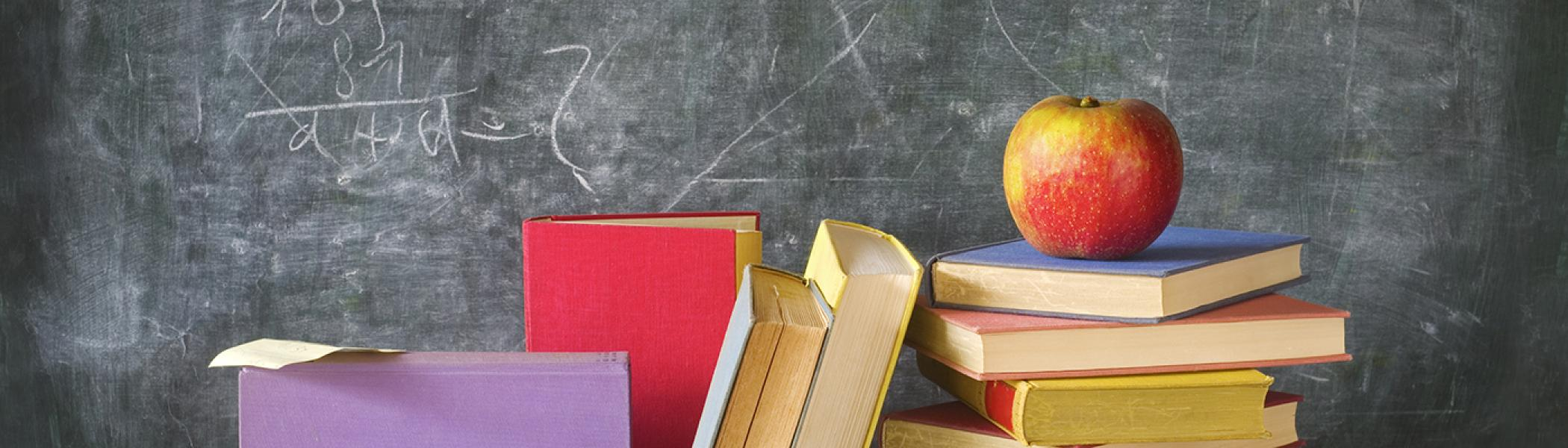 Stack of Textbooks in front of a blackboard