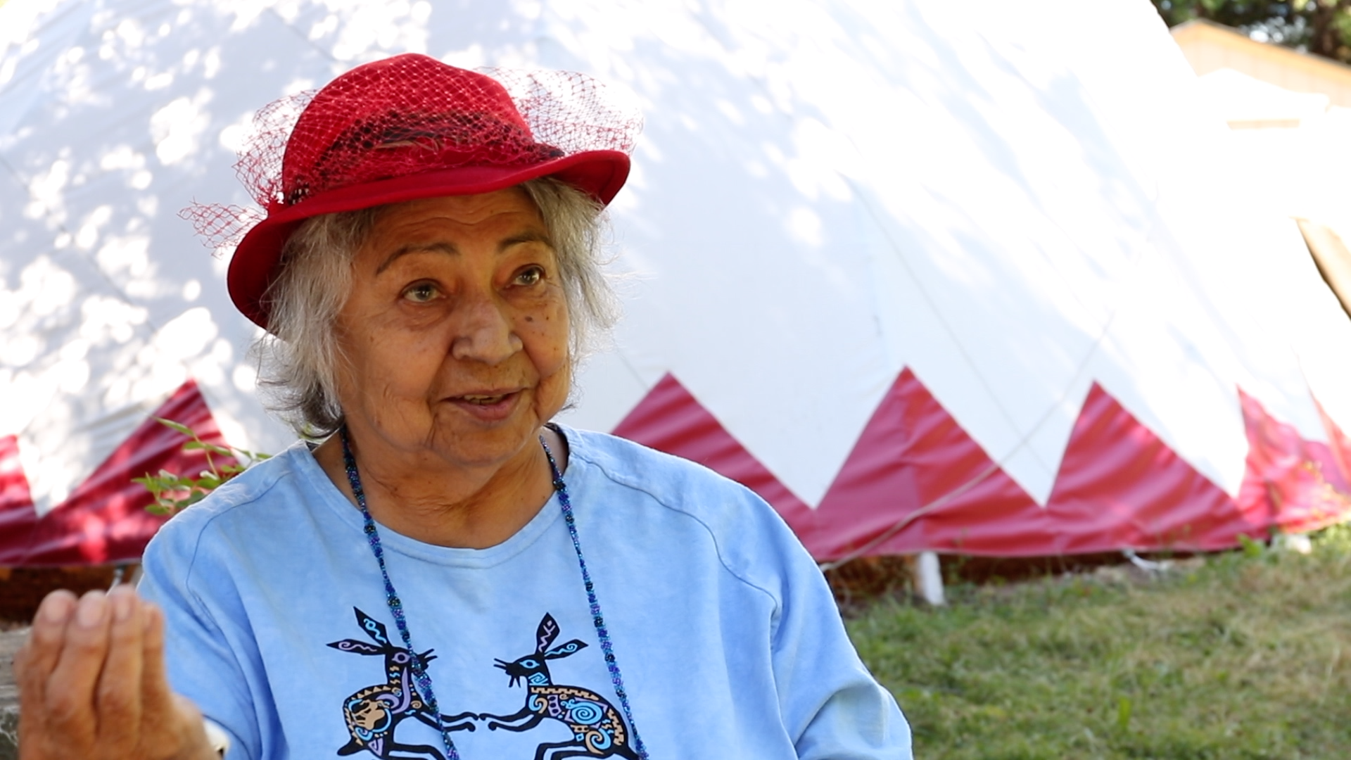 Shirley Williams talking with tipi in the background