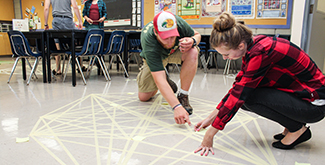 A male and female student crouching on the floor applying tape to the tiles floor of a classroom in a mathematical shape