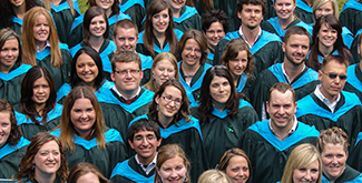 A large group of Teacher Education students wearing their convocation gowns smiling up at the camera for an aerial photo