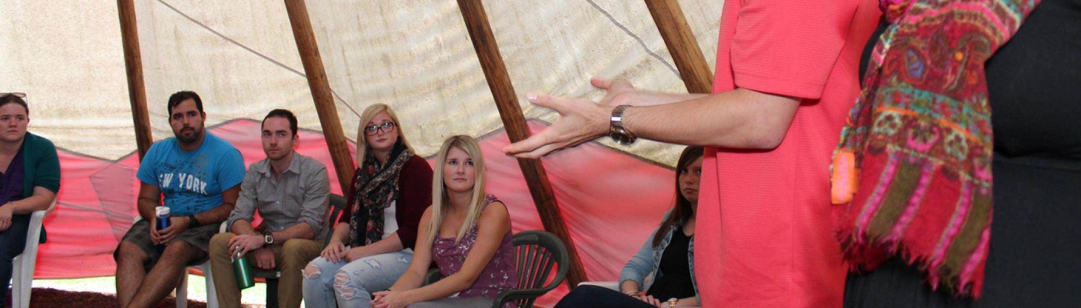 Image of teacher candidates in the school Tipi listening to a fellow Indigenous student share his culture
