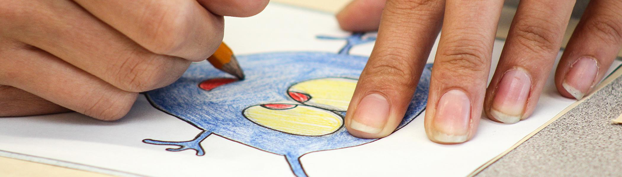 Closeup of a woman's hands colouring in an iluustration on a table
