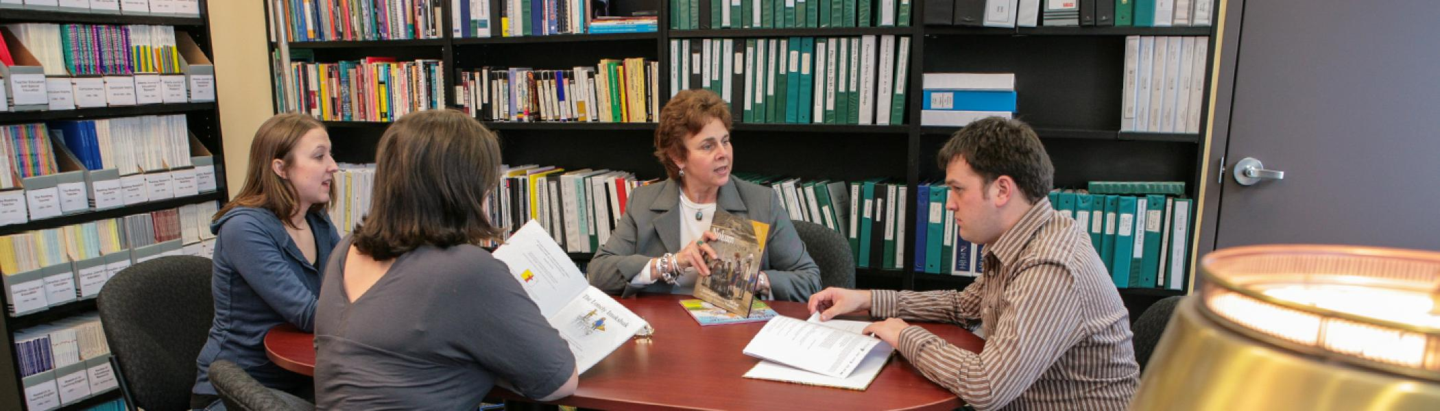 Dr. Deborah Berill sitting at a table with 3 students in an office surrounded by bookcases