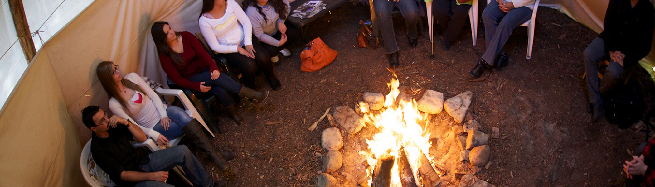 People sitting in a tipi with a fire lit