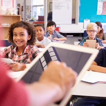 teacher with tablet at front of classroom, students smiling, engaged