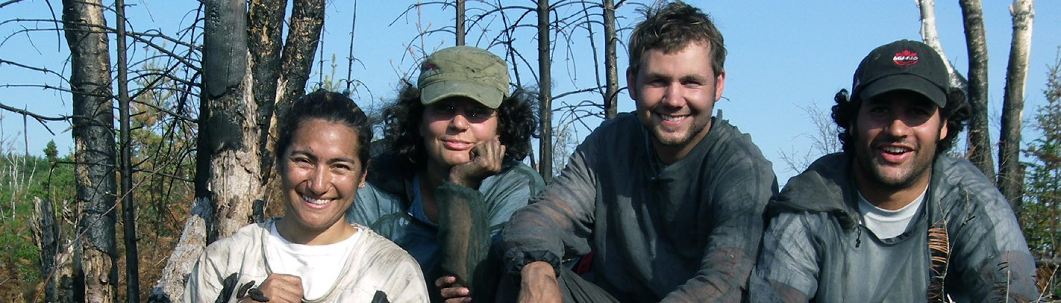 4 grad students smiling at camera covered in dirt and mud