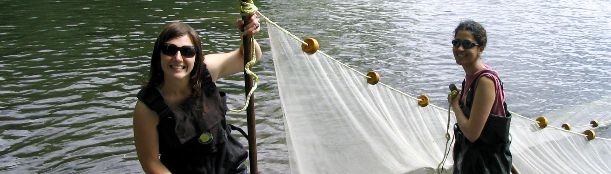 2 female grad students wearing hip waders in water holding net taking samples and smiling at camera with sunglasses on