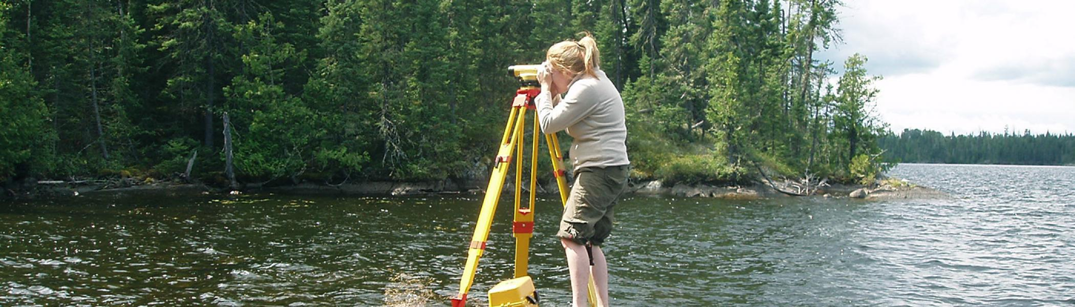 female grad student standing on rock on lake edge looking through tripod doing fieldwork on a sunny day