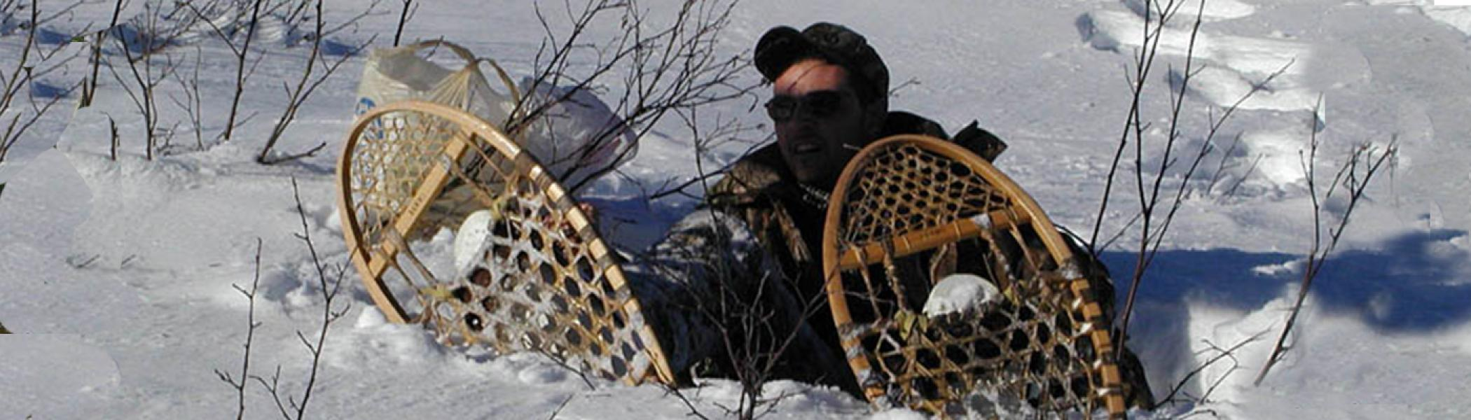 male sitting in deep snow with snow shoes on