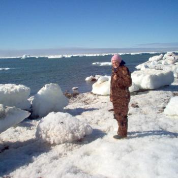 female standing on iceberg with winter camouflage clothing smiling at camera