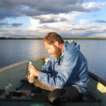 male sitting in boat on cloudy day wearing rain suit taking / analyzing water samples