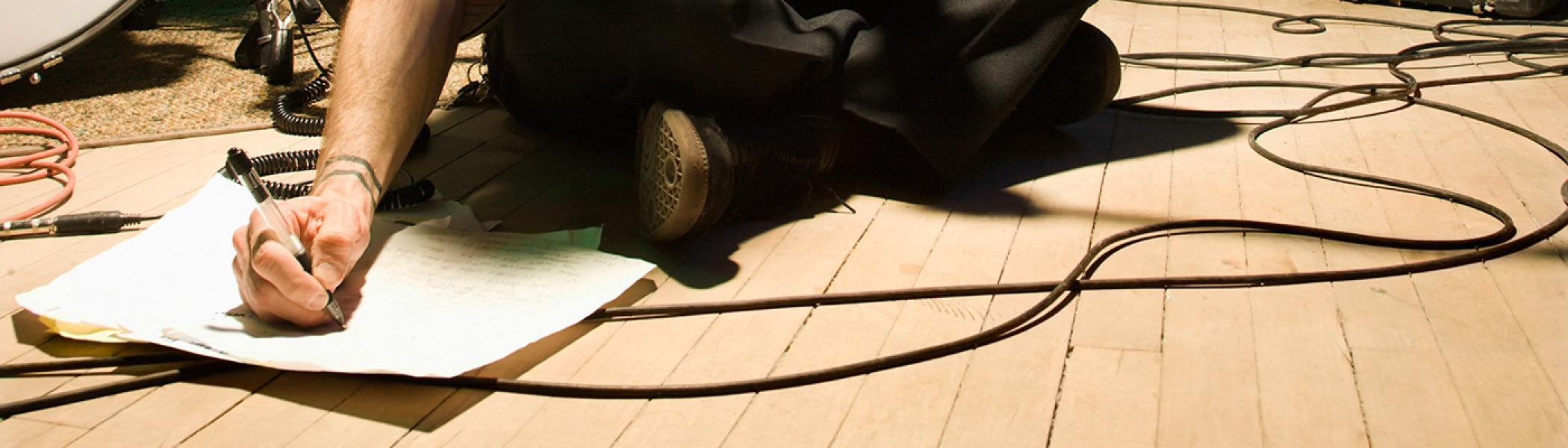 Hand writing on a piece of paper on the floor