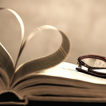 Book open with pages making a heart, glasses