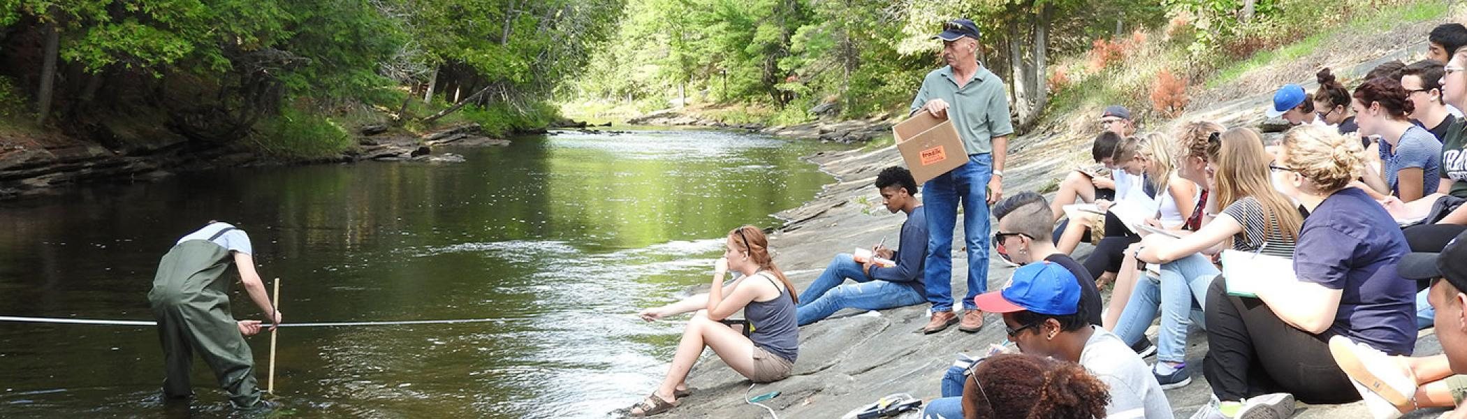 Student working on experiment in river while other students watch