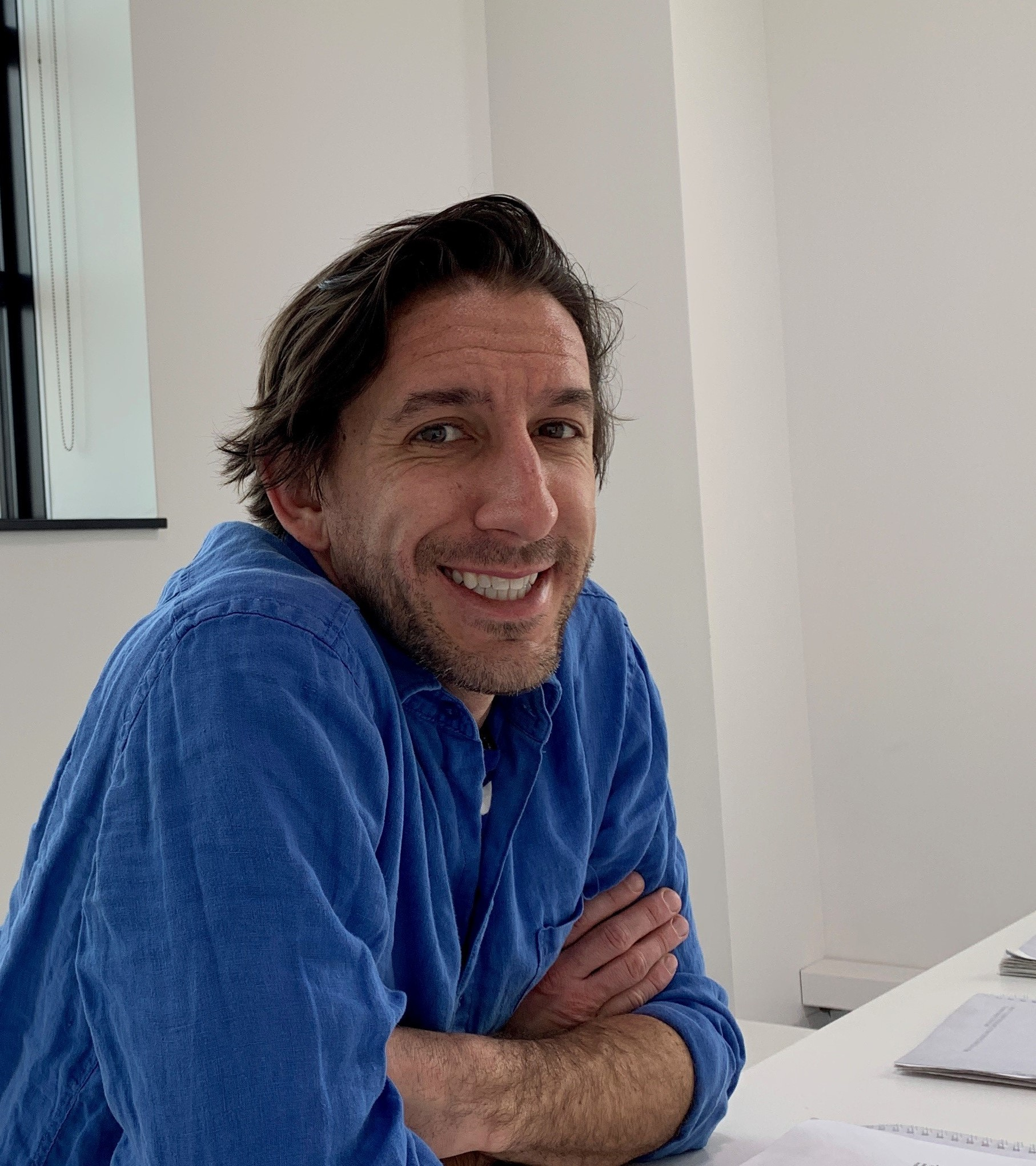 Ryan Sorichetti smiling and sitting at a table with his arms folded