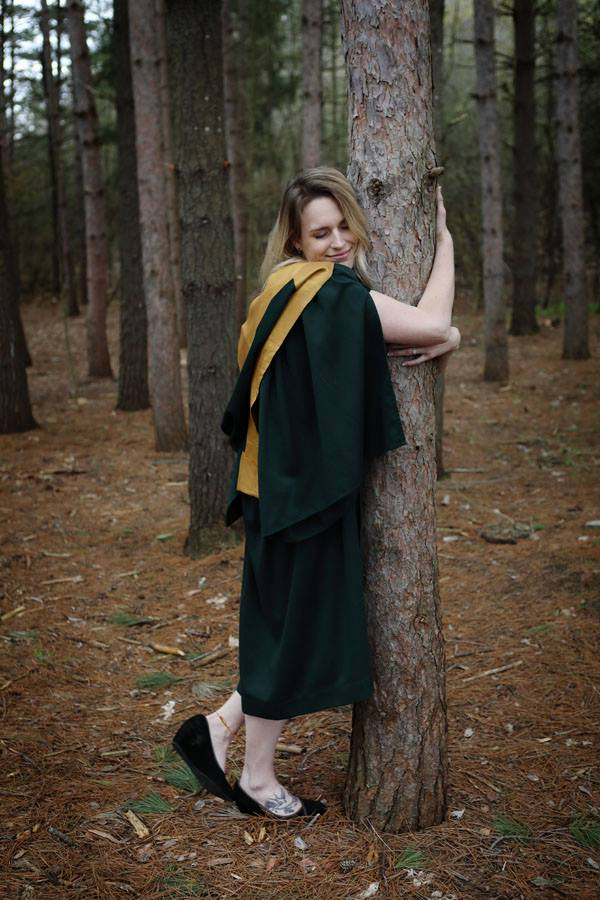 student, Rachel Flinders, wearing graduation gown hugging a tree in forest