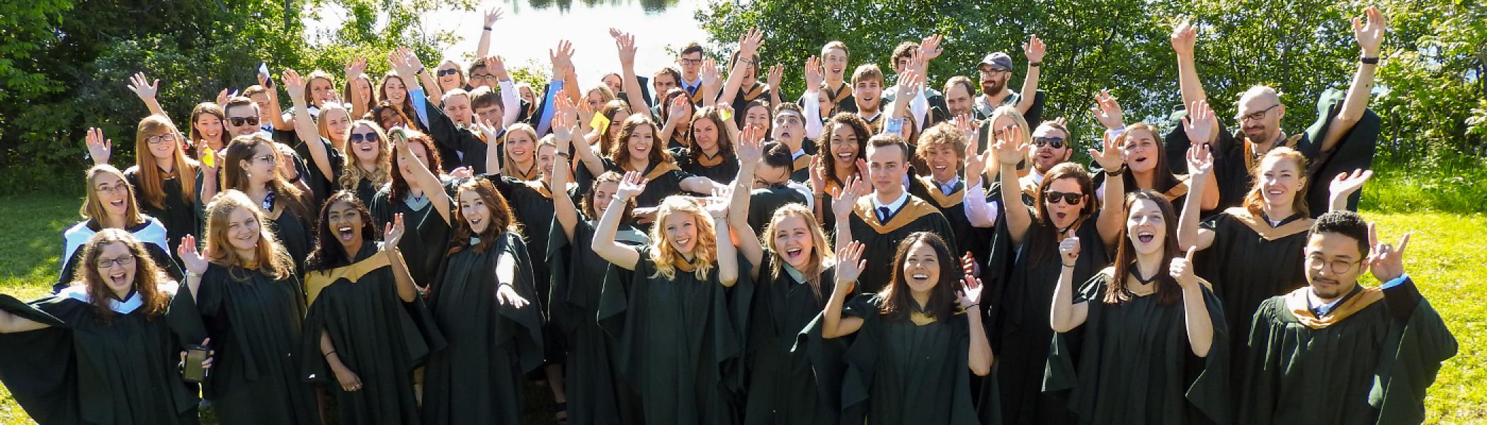 A large group of students standing together in their convocation gowns looking at the camera, smiling