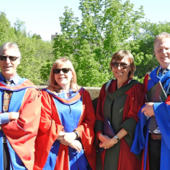 faculty members peter lafleur, cheryl mckenna neuman, catherine eimers and stephen hill at convocation wearing gowns smiling at camera on sunny day