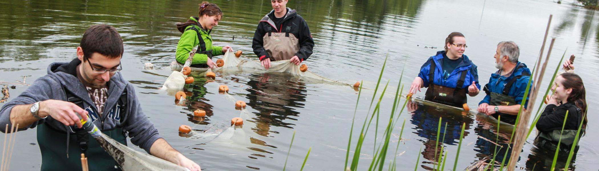 5 students standing in a river with a professor gathering water samples from nets