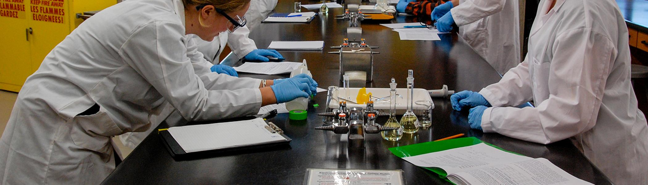 Students in white labcoats mixing samples in test tubes in a lab