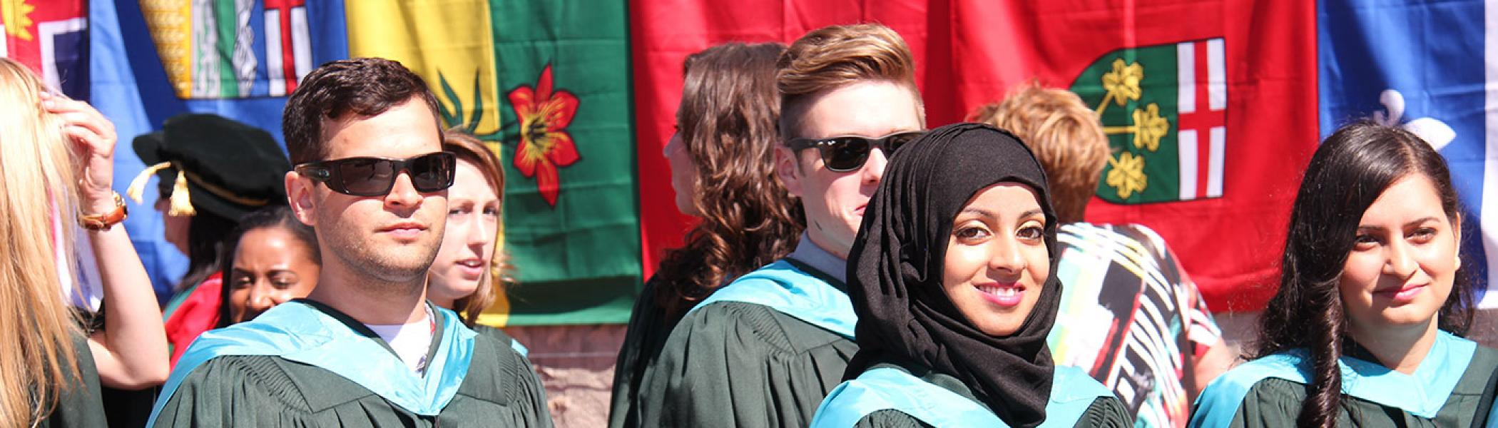 International students standing in front of flags at Convocation