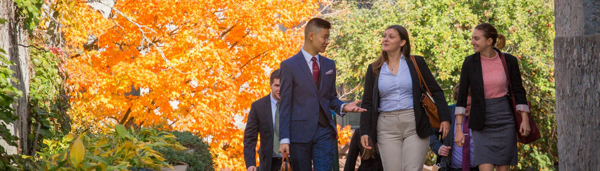 Business students walking up steps, trees with orange leaves behind them.