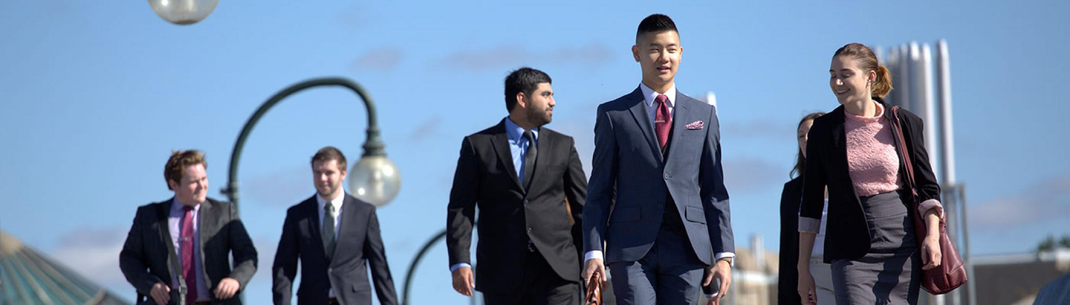 Business students walking across Faryon Bridge in business attire on a sunny day.