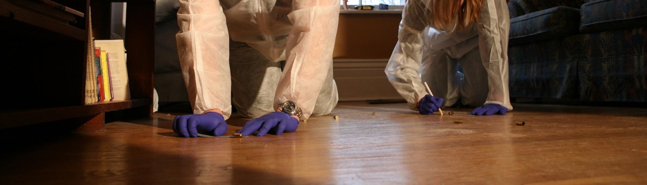 2 people kneeling down in a house investigating something on the floor