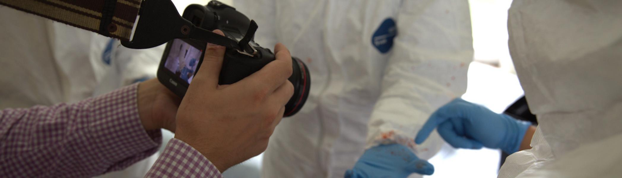 Someone taking a photo of blood on a glove