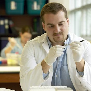 A man in a white lab coat inspecting a glass tube