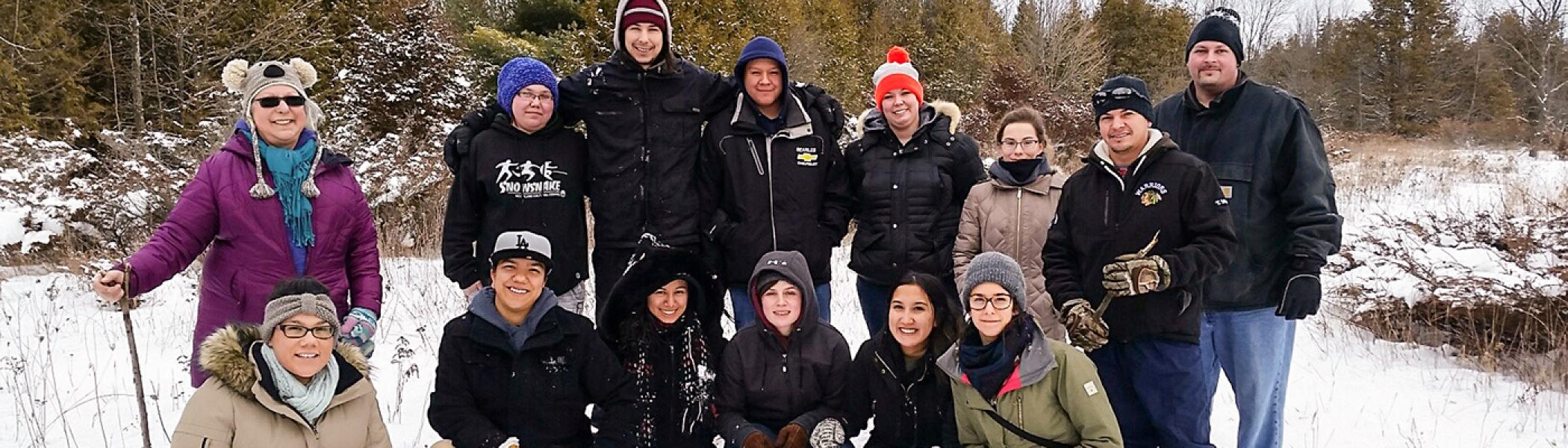 A group of Biishkaa students standing in two rows smiling at the camera, outside in the snow