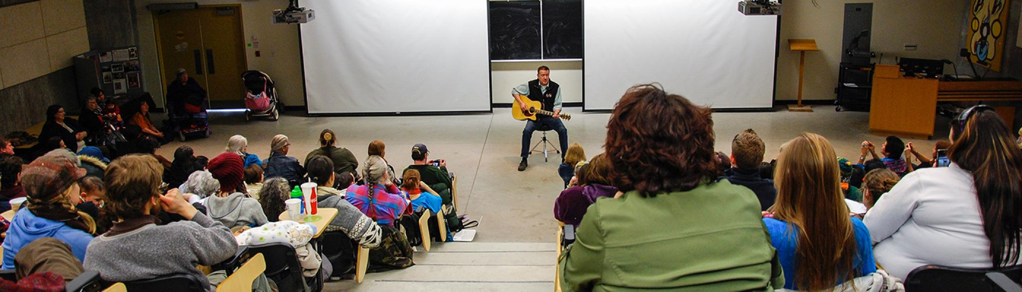 Ton Jackson sitting on a chair in a lecture hall playing guitar to an full audience