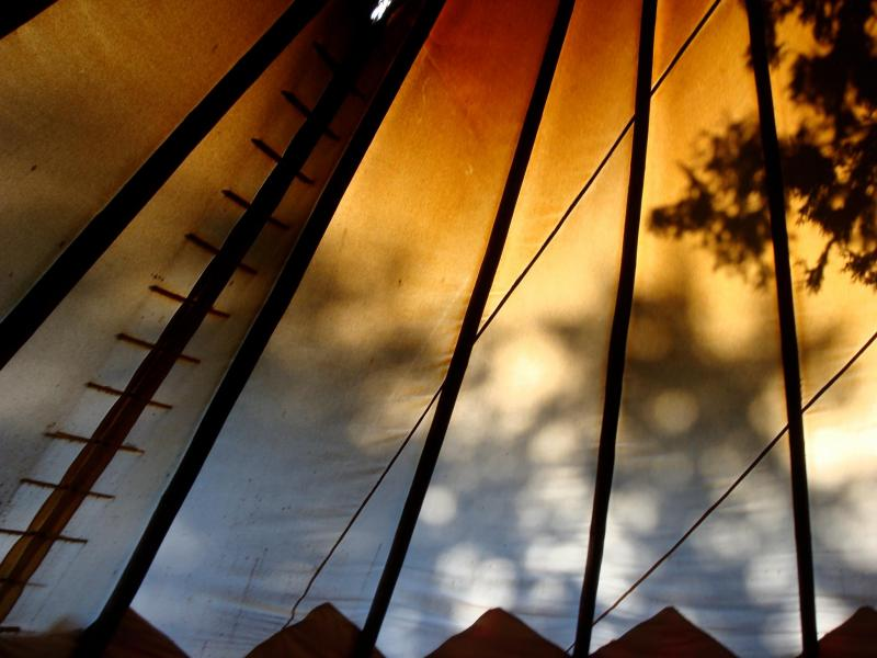 a view of the sun coming through the tipi canvas