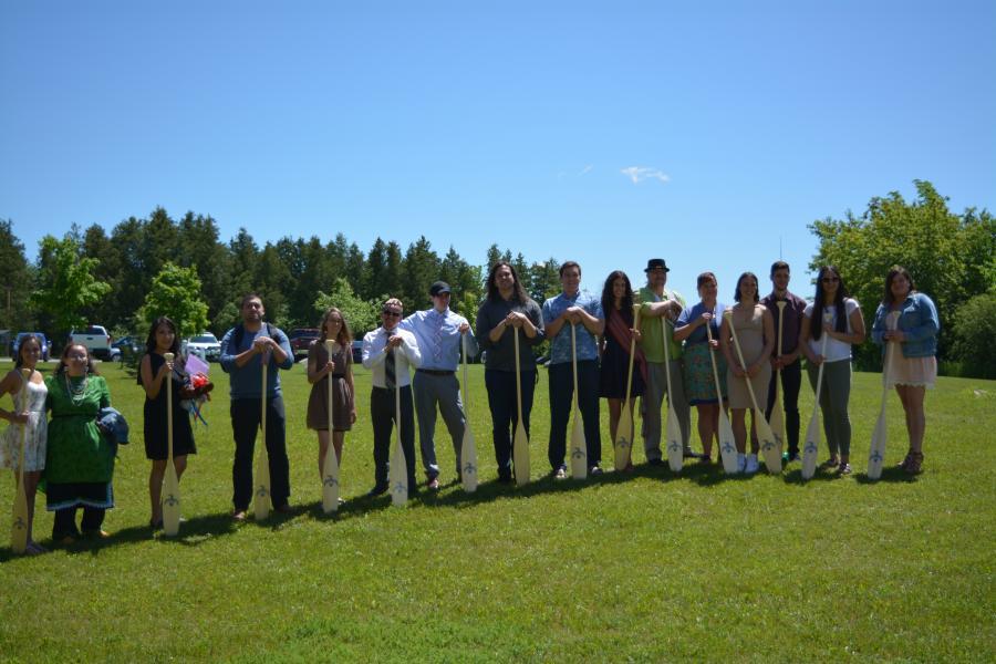 Students holding graduation paddles