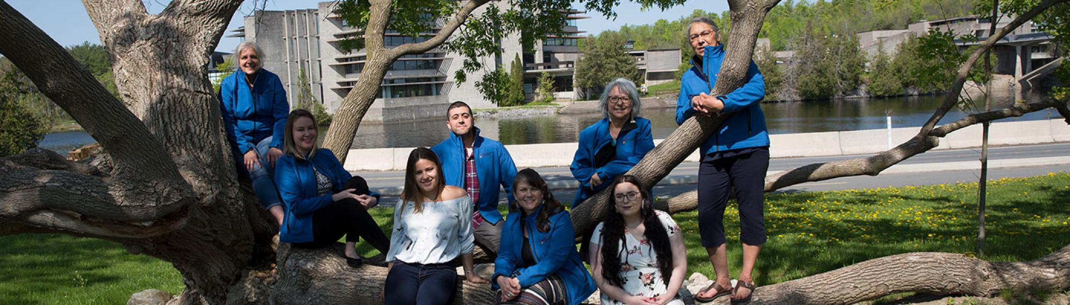 FPHL Department team sitting on a tree outside on a summer day.