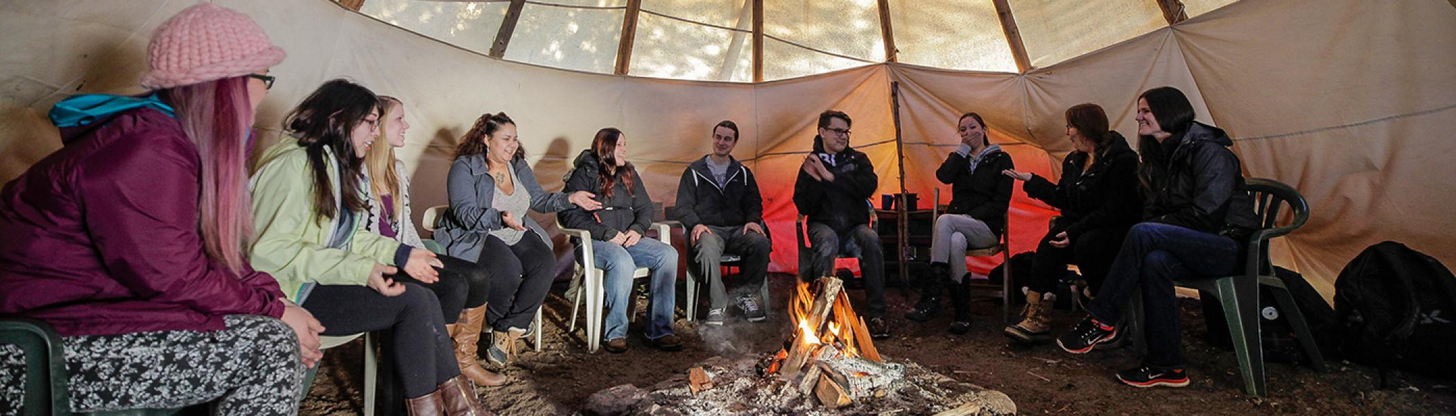 A group of people gather around a fire in a Tipi