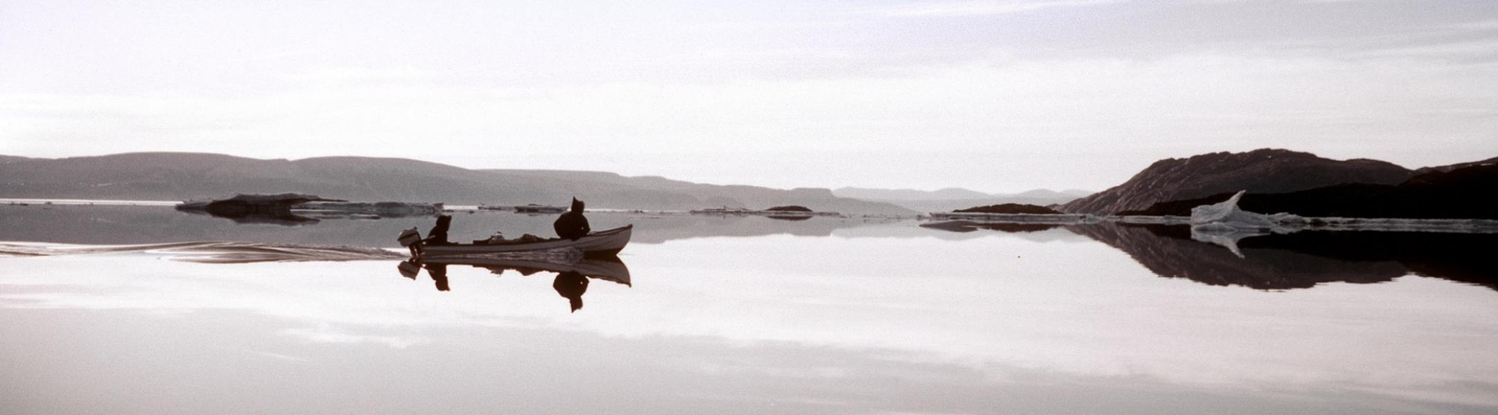 two men in a small motorized boat travel across arctic waters