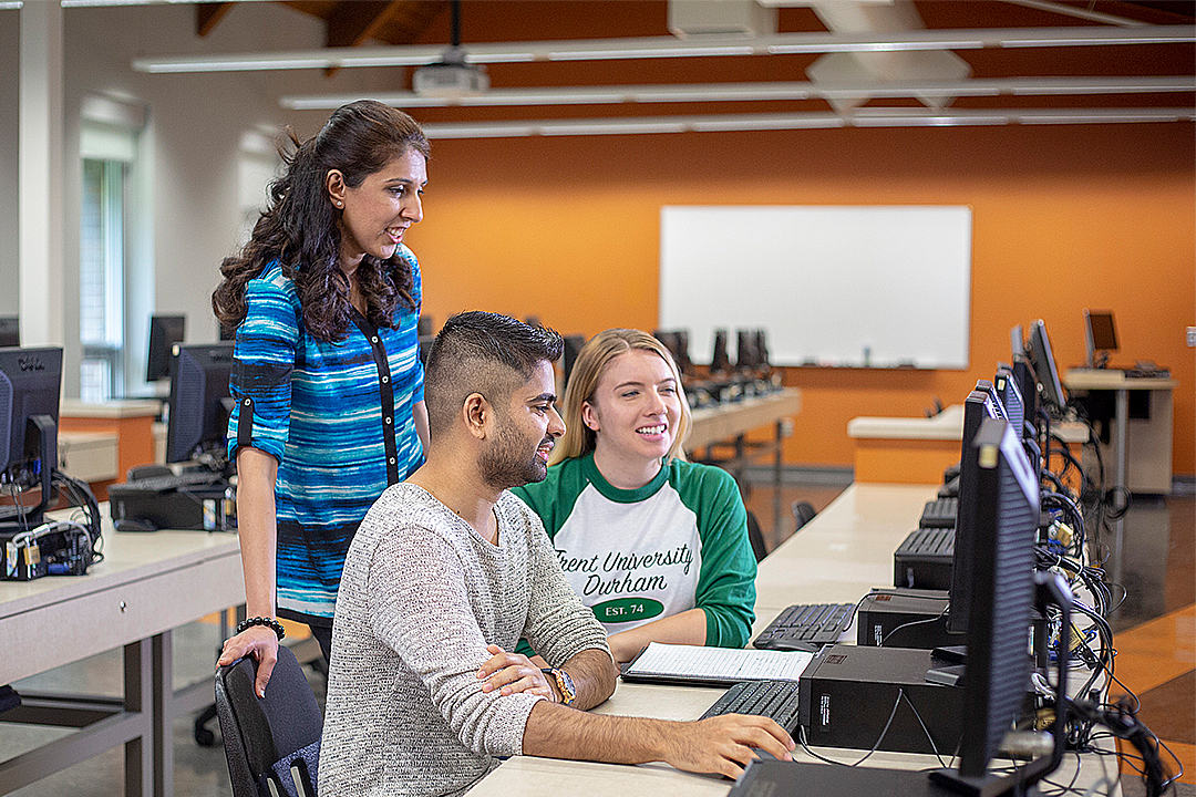 Faculty help two students at a computer