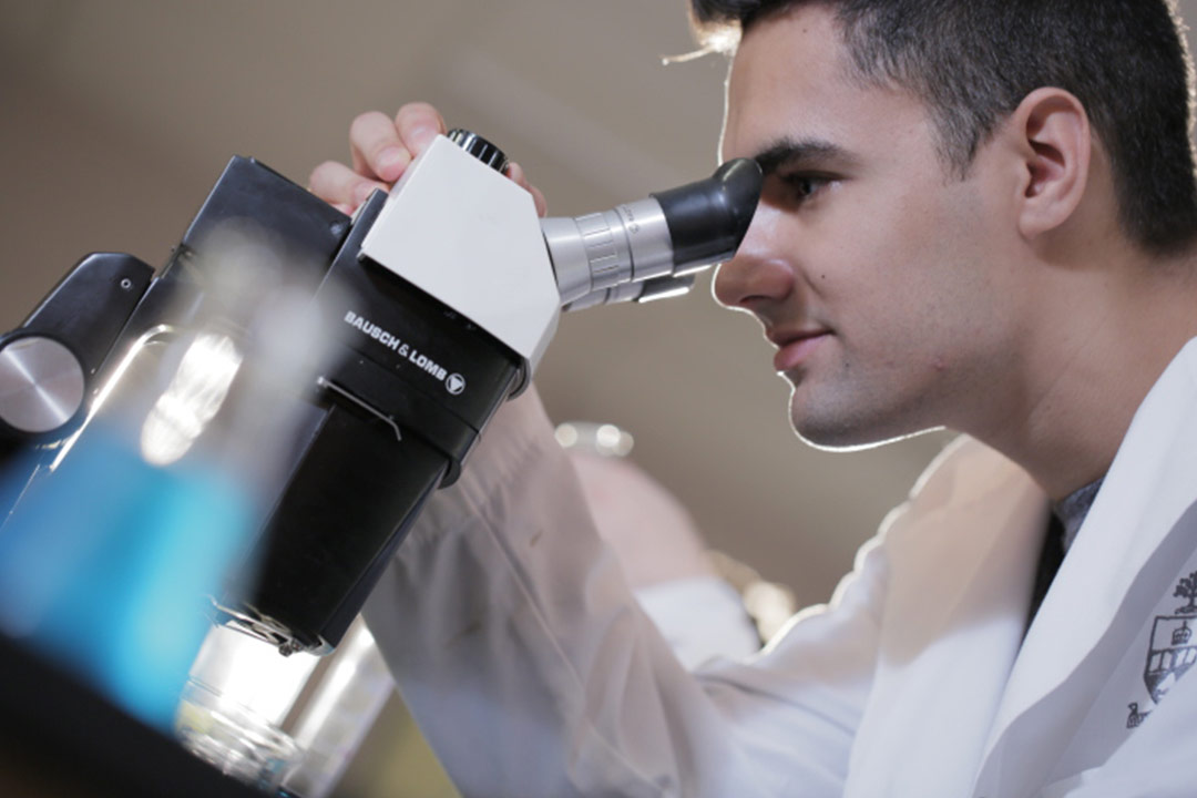 Man in lab coat looking into microscope