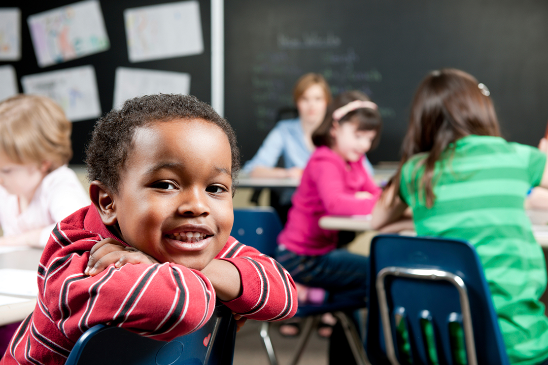 Child in classroom smiling at camera